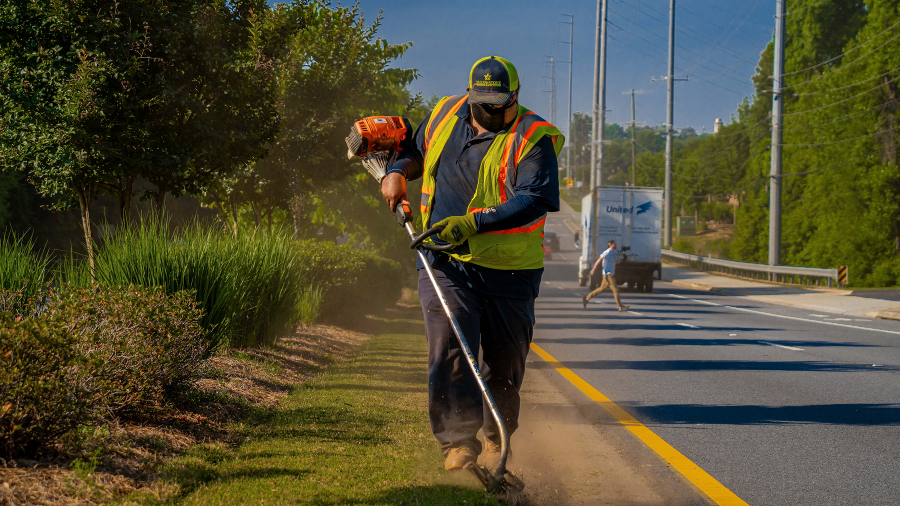Commercial landscaping crew edging along a roadside