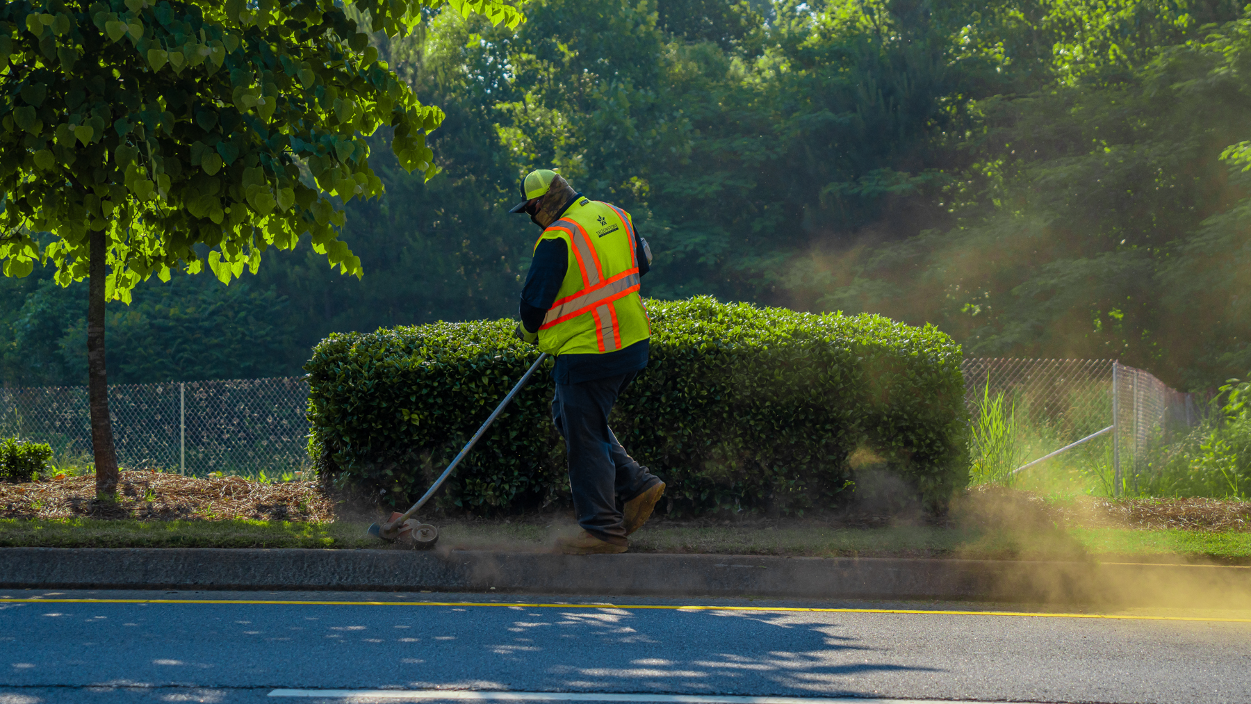 Commercial landscaping maintenance crew trimming along roadside