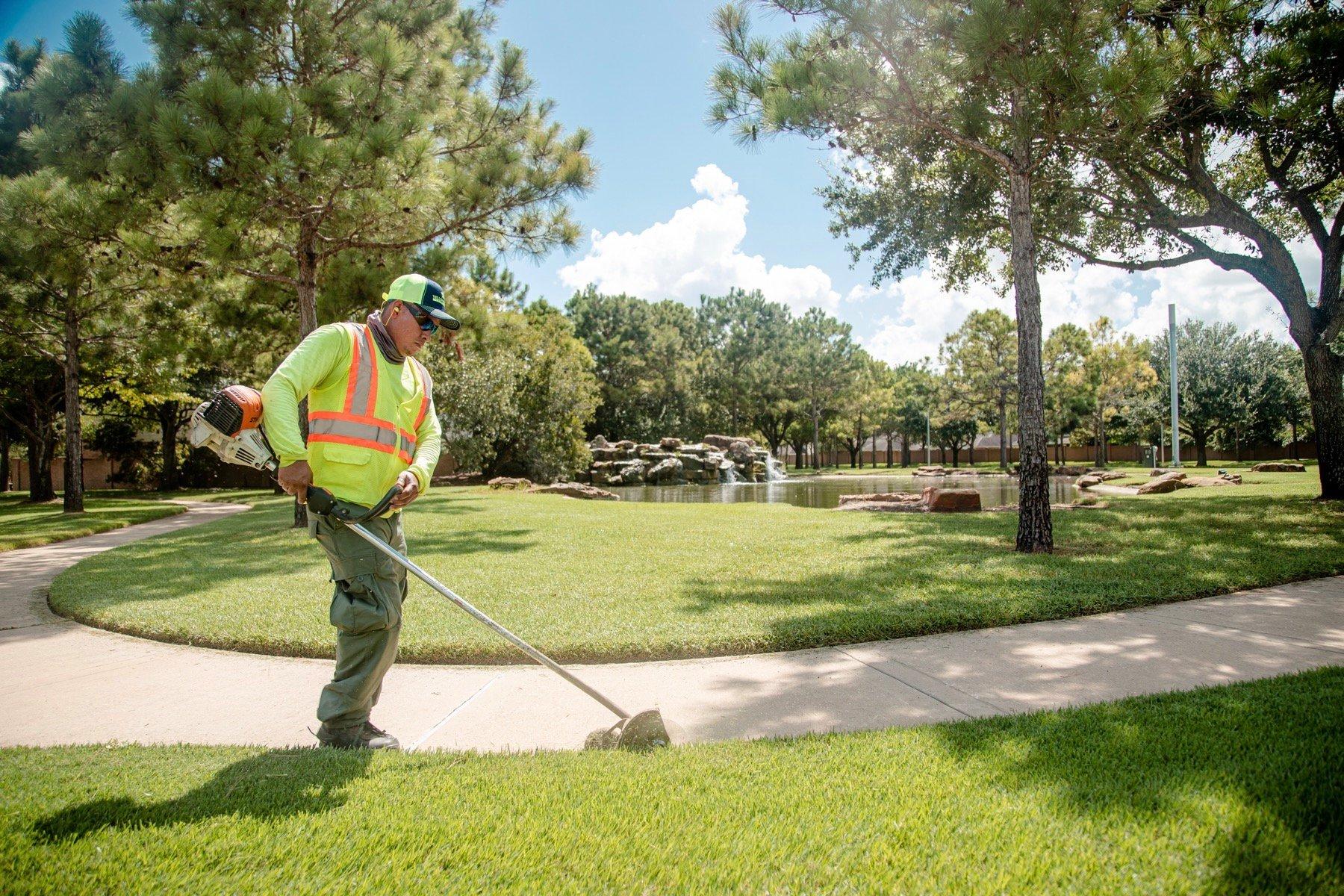 Crew member trimming HOA pathway