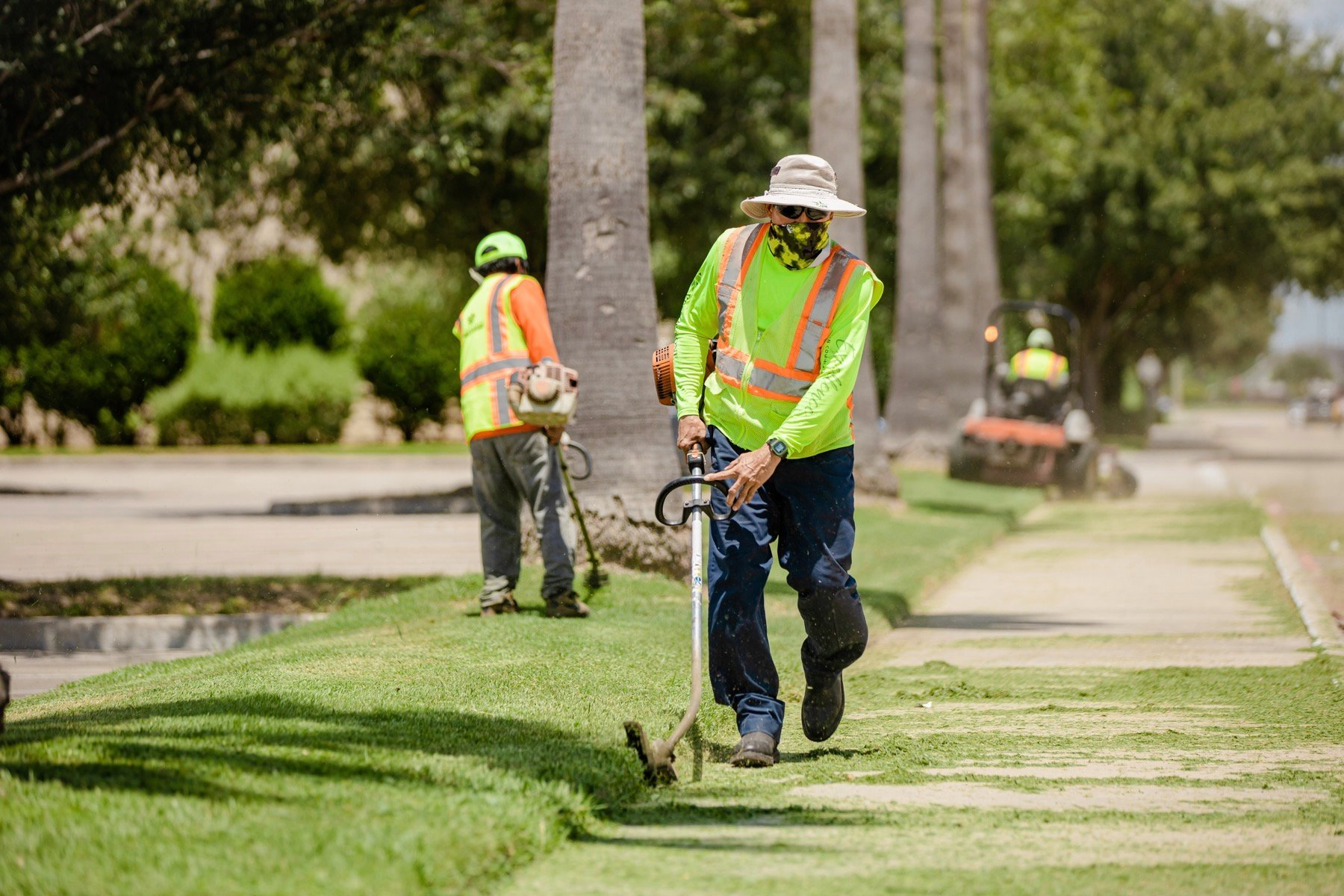 Commercial lawn care crew edging a sidewalk