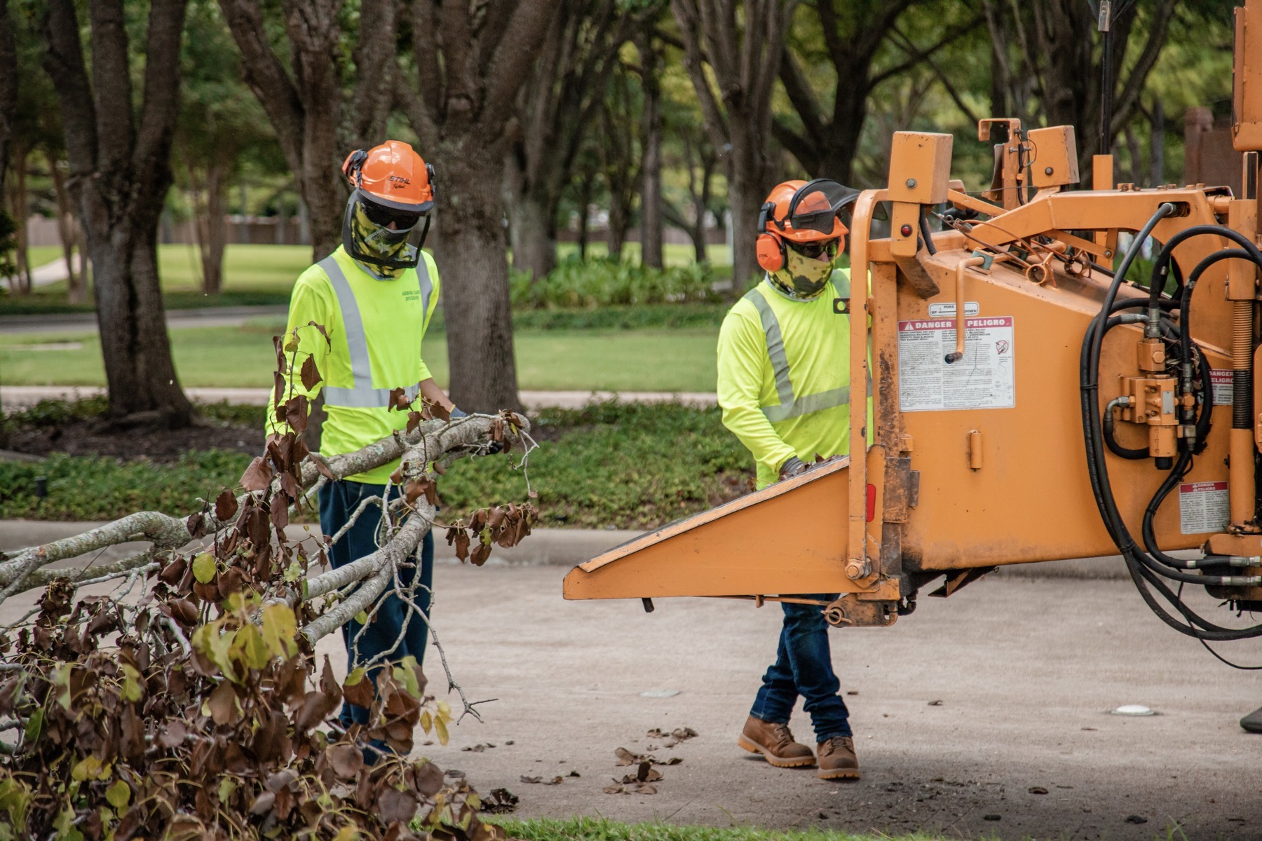 commercial tree service crew using a tree chipper for storm cleanup