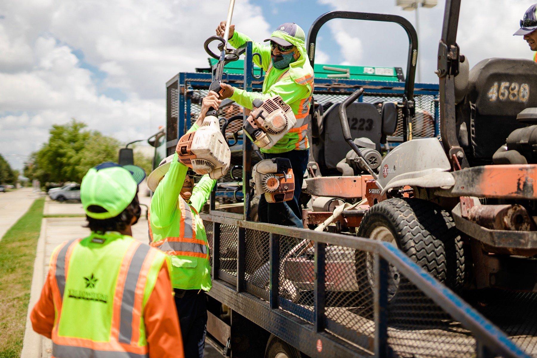 Landscape maintenance crew loading equipment onto a trailer